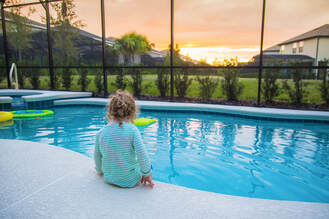 Beautiful sunset in Apopka with girl sitting with her feet in a screen enclosed pool.