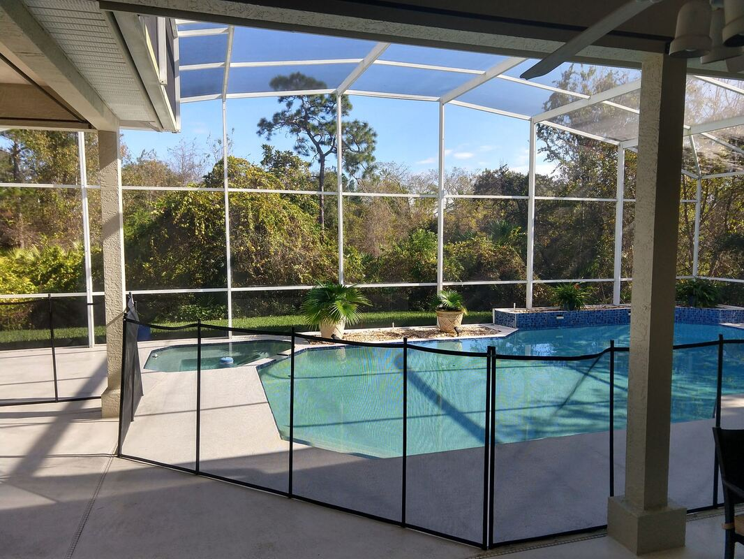 picture showing view from patio of installed pool safety fence around pool in Kissimmee home.